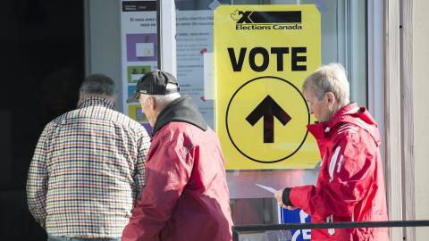 """three people walk past a yellow sign reading """"vote"""""""
