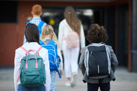 children walk toward a school building