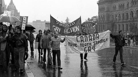 """men carrying a banner reading """"true north strong and gay"""""""