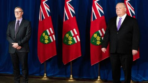 Two men stand in front of some flags of Ontario.