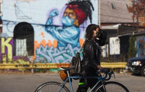 a masked woman walking a bicycle on a city street