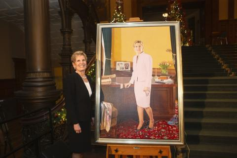 A woman stands beside a portrait