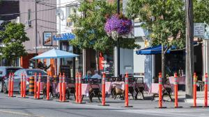 patio tables and umbrellas set up on the road behind pylons from the article The restaurant industry needs a New Deal