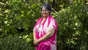 woman in pink dress standing amongst trees from the article 'Invest in healing': Chief RoseAnne Archibald on what the next government must do
