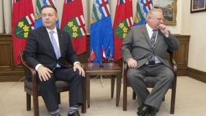 two men in suits sitting in front of a row of flags from the article Ontario needs to take the lessons of the Alberta catastrophe seriously