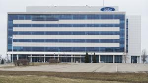 an office building behind an empty parking lot from the article Ford vs. Ford: Will the automaker's investment in electric cars sway a premier who hates them?