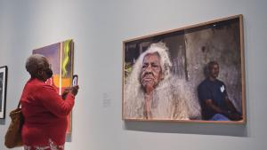 older woman looking at a painting of an older woman from the article 'For us, by us': How a new Caribbean exhibition is changing the AGO