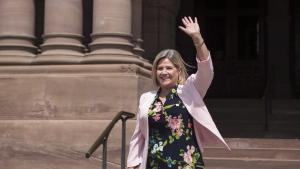 smiling woman in pink jacket and black dress, waving from the article Taking a closer look at the NDP's new attack ads