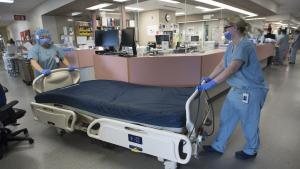 Two staff wheeling a bed through an intensive-care unit from the article Ontario has already hit one of its worst-case COVID-19 scenarios