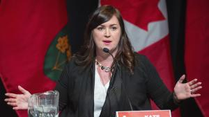 a woman sits in front of flags and behind a microphone from the article What do Ontario Liberals have to offer on housing?