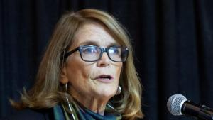 a long-haired woman with glasses behind a microphone from the article The home stretch, Part 3: An education expert on the lessons of COVID-19