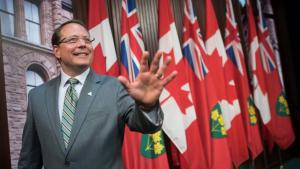 Man smiles and waves as he walks past row of Canadian and Ontario flags.  from the article What's ON: The week ahead in Ontario politics (October 25-29)