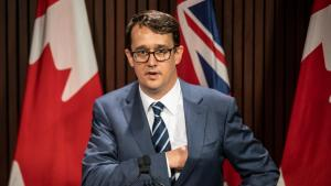 Man reaches into a suit pocket as he steps in front of a microphone.  from the article What's ON: The week that was in Ontario politics (October 18-22)