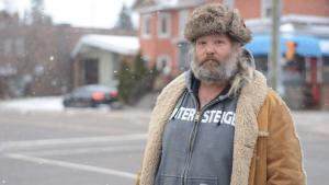 a man in a fur hat stands on a city street from the article This man without a home is advocating for North Bay's homeless population