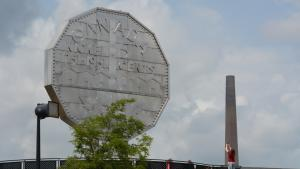giant nickel on the left and smokestack on the right from the article Roadside-attraction showdown: Sudbury's Big Nickel