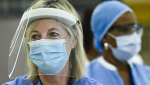 two health-care workers wearing masks and face shields from the article One small, provisional piece of good news about COVID-19 in Ontario