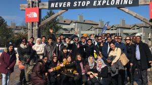 """a group of people stand in front of a sign that reads """"never stop exploring"""" from the article 'In search of a more peaceful environment': Newcomers leave the GTA for new homes up north"""