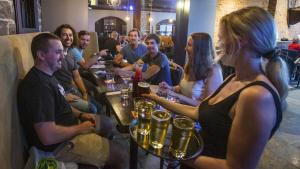 woman with tray of beer stands in front of table with patrons from the article The problems for restaurants won't end when capacity limits are lifted