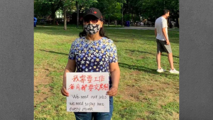 """masked woman holds signs reading """"I need money to pay rent every month"""" from the article 'Who is being targeted?': Advocates condemn proposed massage-parlour bylaw"""