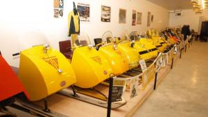 a row of yellow snowmobiles from the article Why this small Ontario town has a snowmobile museum