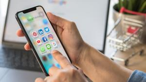 closeup of person holding a phone with social-media apps on it from the article Why Canada must overhaul its approach to regulating online harms
