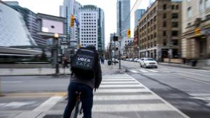 a bike courier on a downtown street from the article Ontario's political leaders need to get tough on food-delivery companies