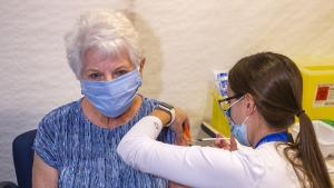 a masked, white-haired woman receives an injection from the article Should Ontario adopt a first-shots-first approach to vaccines?
