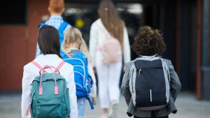 children walk toward a school building from the article Walking the walk: Making the trip to school safe for kids