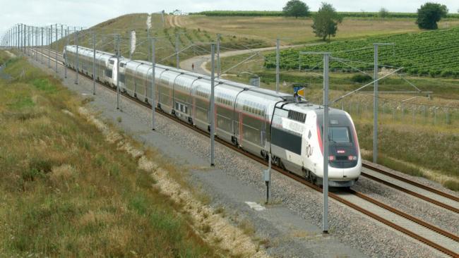 Train passes between rural fields.