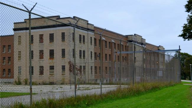 a building behind a fence that's part of the Guelph Correctional Institute