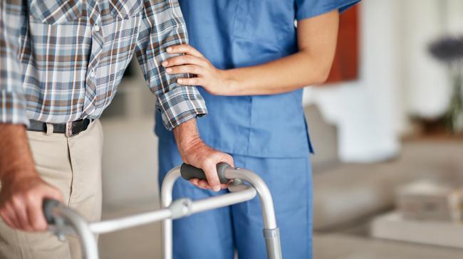 Nurse guides an elderly man using a walker.
