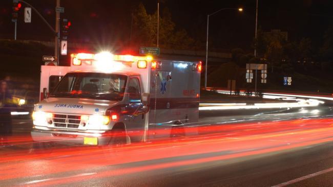 ambulance driving through traffic at night