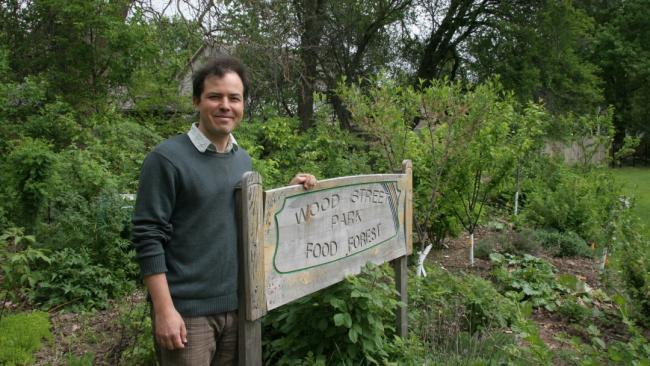 a person standing in front of a sign indicating a food forest