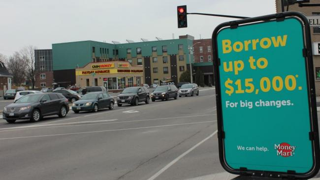 a green sign on the street advertising a cash day loan location