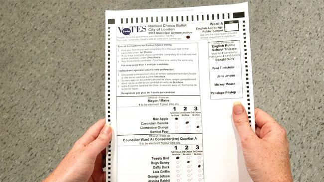 Two hands hold a paper ballot.