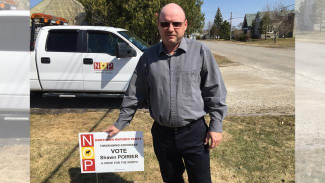 an election candidate showing off his lawn sign