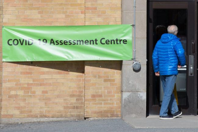 a man walks into a COVID-19 assessment centre