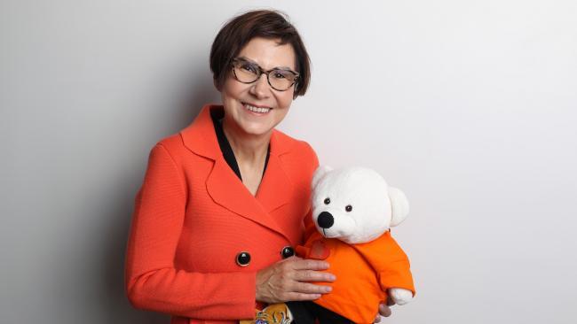 smiling woman in an orange blazer holding a teddy bear also wearing orange