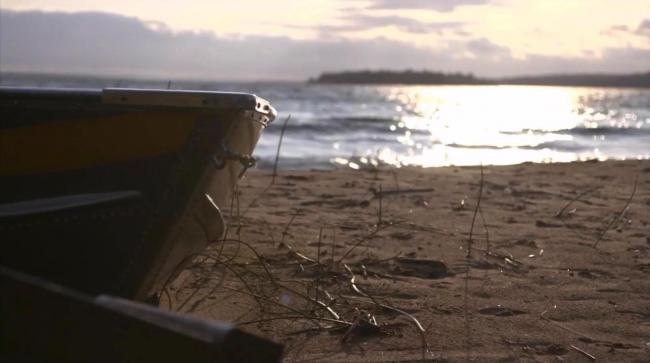 Bow of rowboat on beach with sunlit water in the background.