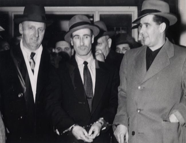 A man in handcuffs is flanked by two policemen
