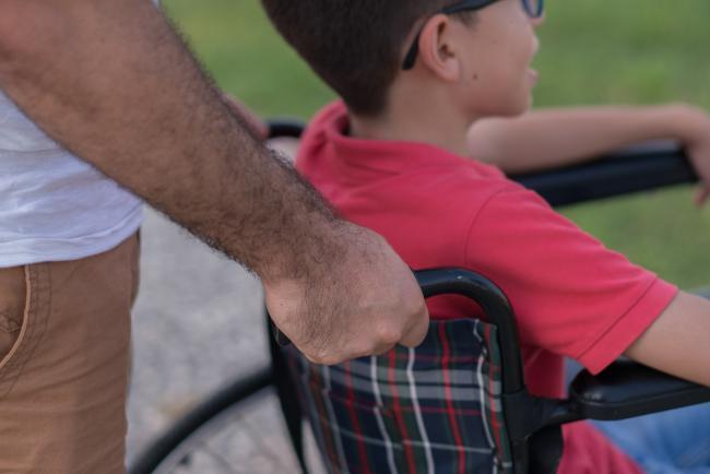 man pushing child in wheelchair