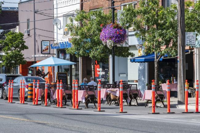 patio tables and umbrellas set up on the road behind pylons