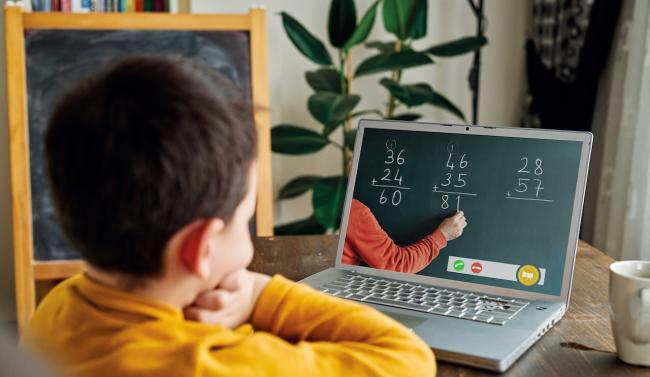 a child in a yellow sweater watches a mass lesson on a laptop