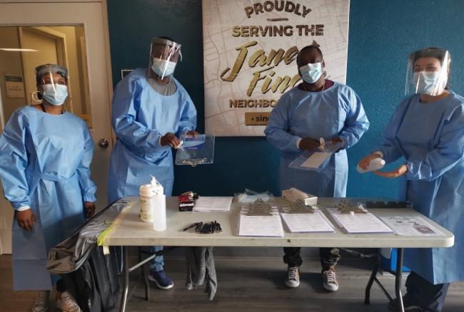 women wearing masks and scrubs stand around a table