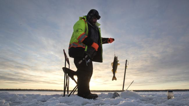 man in reflective vest ice fishing