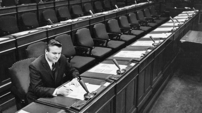 black and white photo of a man sitting in behind a long counter