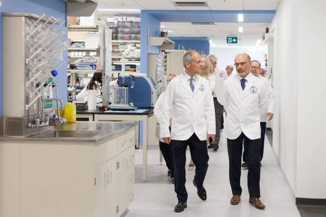 two men in white coats walk through a lab
