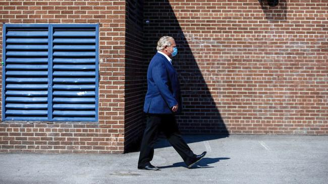 mask-wearing man walks by a school building