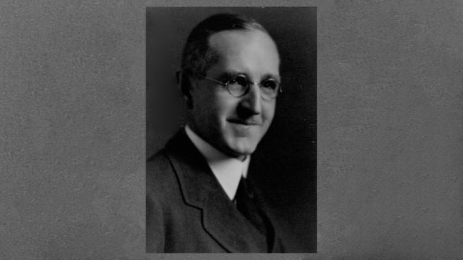 black and white photo of a man wearing suit and glasses
