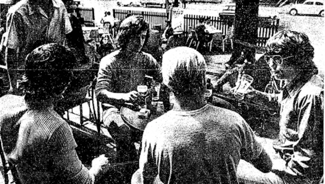 black and white photo of young men drinking